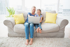 Madre e figlia felici che per mezzo del computer portatile sul sofà Fotografia Stock