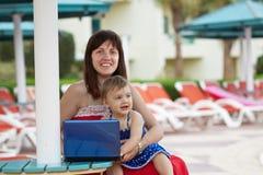 Madre e figlia felici con il computer portatile Immagini Stock