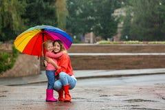 Madre e figlia felici con l'ombrello luminoso sotto pioggia fotografia stock libera da diritti