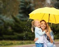 Madre e figlia felici con l'ombrello sotto pioggia immagini stock libere da diritti