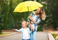 Madre e figlia felici con l'ombrello sotto pioggia immagini stock