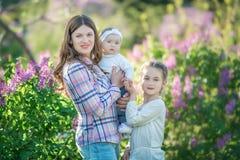 Madre e figlia felici con le mele verdi nel giardino dei lillà di fioritura fotografia stock libera da diritti
