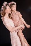 Madre e figlia felici in corone e vestiti floreali da rosa Immagini Stock