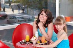 Madre e figlia felici in ristorante. Immagine Stock Libera da Diritti