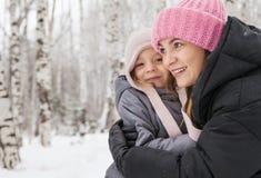 Madre e figlia felici in una foresta di inverno Fotografia Stock