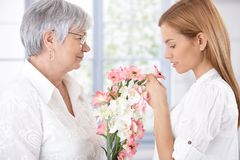 Madre e figlia maggiori con i fiori Immagini Stock