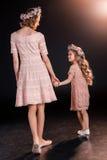 Madre e figlia nel tenersi per mano floreale delle corone Fotografia Stock
