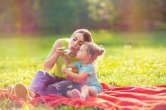Madre e figlia nella schiuma della minestra dei colpi del parco e fare le bolle immagine stock
