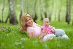 Madre e figlia nella sosta della sorgente della betulla Immagine Stock