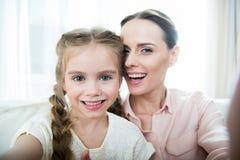 Madre e figlia sorridenti che fanno selfie Fotografia Stock
