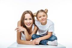 Madre e figlia sorridenti divertendosi insieme ed esaminare macchina fotografica immagine stock