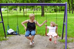 Madre e figlia su oscillazione Immagine Stock