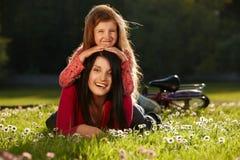 Madre e figlia su un'erba immagini stock