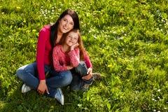 Madre e figlia su un'erba immagine stock libera da diritti