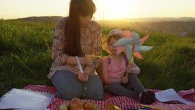 Madre e figlia su un picnic su una collina di estate al tramonto archivi video