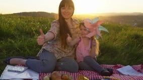 Madre e figlia su un picnic su una collina di estate al tramonto video d archivio