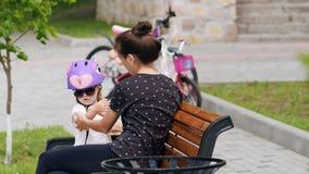 Madre e figlia sul banco in parco video d archivio