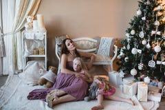 Madre e figlia vicino all'albero di Natale, abbracciante, preparazione per il Natale, decorazione, decorazione, stile di vita, fa Fotografia Stock