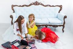 Madre e figlie che fanno trucco Fotografie Stock Libere da Diritti