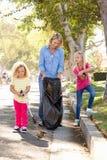 Madre e figlie che prendono lettiera in via suburbana immagine stock libera da diritti