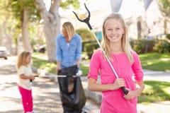 Madre e figlie che prendono lettiera in via suburbana immagini stock