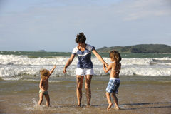 Madre e figlie felici divertendosi sulla spiaggia immagini stock libere da diritti