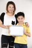 Madre e figlio asiatici con la macchina fotografica in bianco di sguardo e del bordo bianco Fotografia Stock