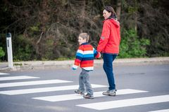 Madre e figlio che attraversano la via Immagini Stock Libere da Diritti