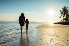 Madre e figlio che camminano lungo la bella spiaggia durante l'alba fotografia stock libera da diritti