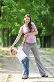 Madre e figlio che camminano nella sosta Immagine Stock