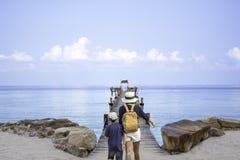 Madre e figlio che camminano sul crogiolo di pilastro del ponte di legno nel mare e sul cielo luminoso a Koh Kood, Trat in Tailan fotografie stock