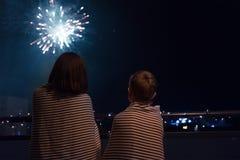 Madre e figlio che esaminano i fuochi d'artificio di celebrazione del nuovo anno dentro vicino fotografie stock