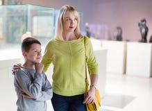 Madre e figlio che esaminano le esposizioni in museo fotografie stock libere da diritti