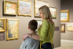 Madre e figlio che esaminano le pitture in corridoi del museo immagini stock