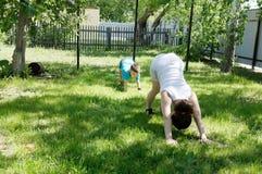Madre e figlio che fanno gli esercizi di yoga su erba nell'iarda al tempo di giorno La gente divertendosi all'aperto Fotografie Stock Libere da Diritti