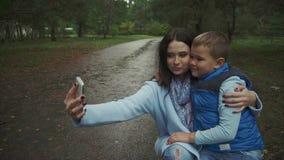 Madre e figlio che fanno selfie nel parco di autunno stock footage