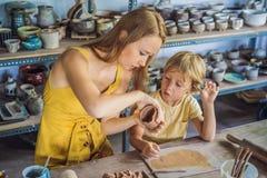 Madre e figlio che fanno vaso ceramico nell'officina delle terraglie fotografia stock