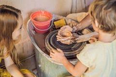 Madre e figlio che fanno vaso ceramico nell'officina delle terraglie immagine stock libera da diritti