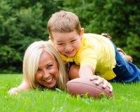 Madre e figlio che giocano a calcio all'aperto Fotografie Stock