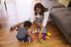 Madre e figlio che giocano con i giocattoli sul pavimento a casa Immagine Stock Libera da Diritti