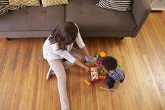 Madre e figlio che giocano con i giocattoli sul pavimento a casa Fotografia Stock Libera da Diritti