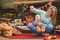 Madre e figlio che giocano nell'iarda nel villaggio Fotografia Stock