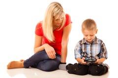Madre e figlio che giocano video gioco sullo smartphone Immagini Stock Libere da Diritti