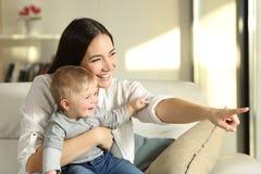 Madre e figlio che guardano attraverso una finestra a casa Fotografia Stock