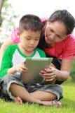 Madre e figlio che per mezzo di un ridurre in pani Fotografia Stock Libera da Diritti