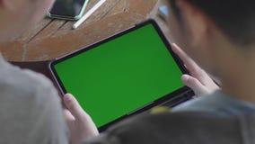 Madre e figlio che per mezzo insieme della compressa digitale, chiave verde di intensità dello schermo video d archivio