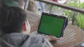 Madre e figlio che per mezzo insieme della compressa digitale, chiave verde di intensità dello schermo archivi video