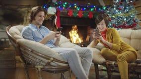 Madre e figlio che praticano il surfing Internet sugli smartphones nella notte e nella risata di natale video d archivio