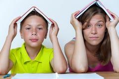 Madre e figlio che si siedono alla tavola con i libri Fotografia Stock
