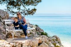 Madre e figlio che si siedono sul banco alla spiaggia rocciosa Fotografie Stock